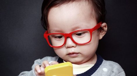 Picture of a young bespectaled child using a mobile device